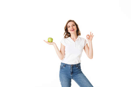 Portrait of young beautiful lady standing with green apple in hand, and happily looking in camera while showing ok gesture on white background isolated