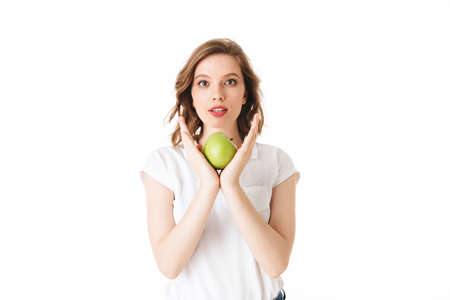 Portrait of young pensive lady standing with green apple in hand and dreamily looking in camera on white background isolated.