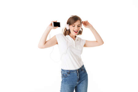 Portrait of beautiful lady in headphones happily dancing with cellphone in hand on white background isolated.