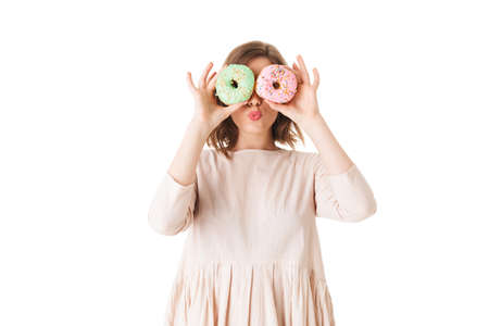 Portrait of cute lady in pink dress standing and covering her eyes with donuts on white background isolated.