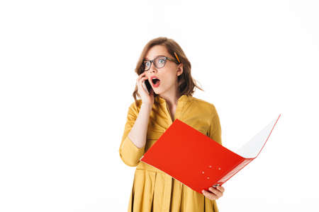 Portrait of young shocked lady in eyeglasses standing with cellphone and open red folder in hands, while amazedly looking aside on white background isolated