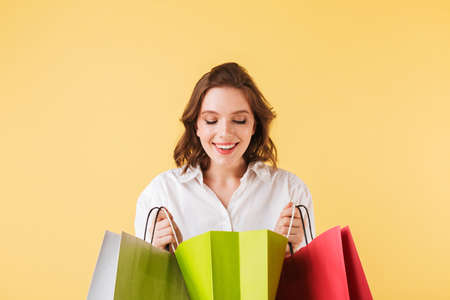 Young pretty lady standing and joyfully looking in open colorful shopping bags on over yellow background. Фото со стока