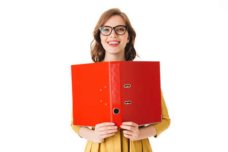 Portrait of young joyful lady in eyeglasses standing with open red folder in hand, and happily looking in camera on white background isolated