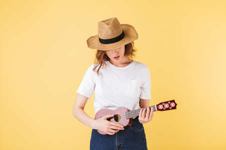 Portrait of pretty lady in straw hat standing with little guitar and playing on it on over pink background. Фото со стока