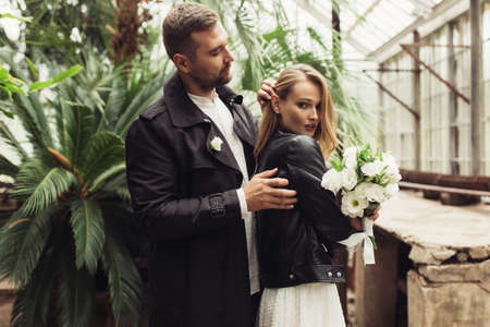Young attractive woman in black leather jacket and dress with little bouquet of white flowers in hand, thoughtfully looking in camera handsome man standing behind straighten her hair in old greenhouse Imagens