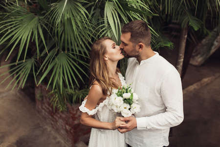 Young attractive groom in shirt and beautiful bride in white dress with little bouquet of flowers in hand, thoughtfully taking photo on cellphone spending time together in greenhouse