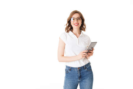 Portrait of young beautiful lady in eyeglasses standing with the tablet in hands and happily looking in camera on white background isolated. Фото со стока