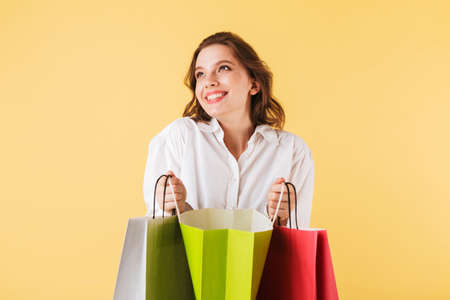 Beautiful smiling and amazed lady standing and happily looking aside while holding open colorful shopping bags on over yellow background. Фото со стока