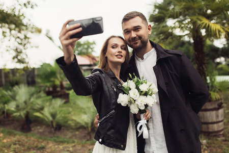 Young joyful man in trench coat and beautiful smiling woman in black leather jacket and dress, with little bridal bouquet of flowers in hand taking photo on cellphone in cozy garden of greenhouse