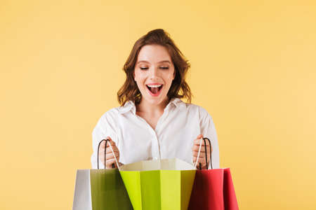 Portrait of young joyful lady standing and happily looking in open colorful shopping bags on over pink background.