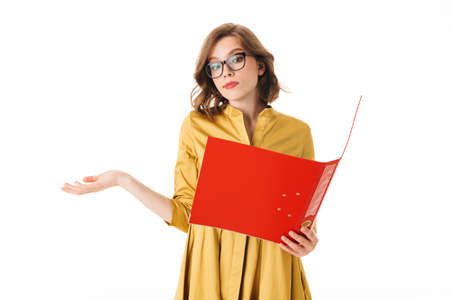 Portrait of pretty lady in eyeglasses standing and thoughtfully looking in open red folder on white background isolated.
