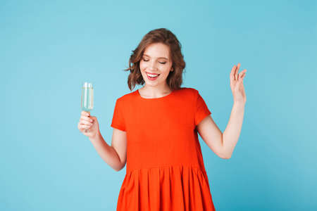 Beautiful lady in red dress standing with champagne and happily looking aside over colorful background.