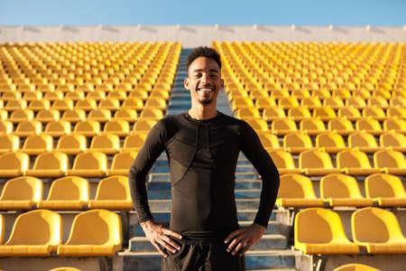 Young joyful African American sportsman happily looking in camera among empty stadium seats