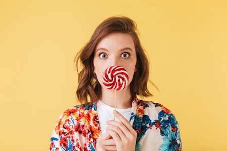 Portrait of young lady in colorful shirt standing and covering her lips with lollipop candy, while amazedly looking in camera on over pink background