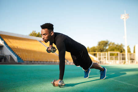 Young strong serious African American sportsman doing exercises with dumbbells at stadium