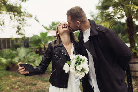 Young attractive man in trench coat kissing in cheek cheeful woman in black leather jacket and dress, with little bridal bouquet of white flowers and cellphone in hands in cozy garden of greenhouse Imagens - 147581885
