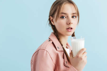 Young beautiful girl with two braids in pink leather jacket with milk mustache holding glass in hand dreamily looking in camera over blue background