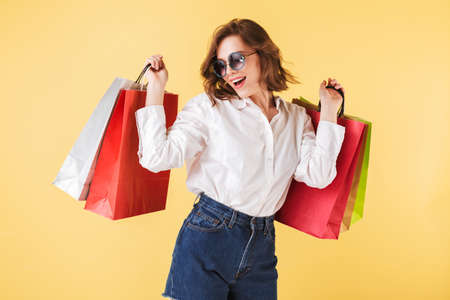Portrait of happy lady in sunglasses standing with colorful shopping bags in hands on over pink background. Young woman standing in white shirt and denim shorts