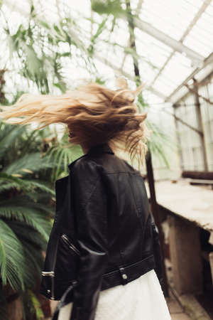 Young beautiful woman from back in black leather jacket and white dress dreamily whirling in old cozy greenhouse