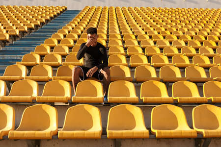 Young handsome African American sportsman covering face with hand resting after run among empty stadium seats
