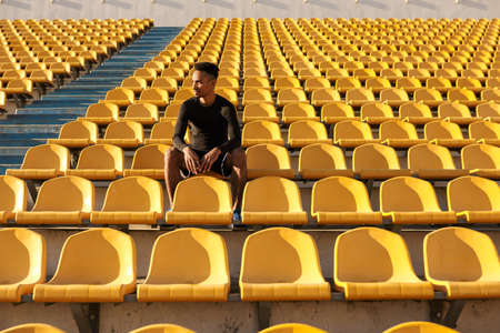 Young confident African American sportsman thoughtfully resting after run among empty stadium seats Imagens