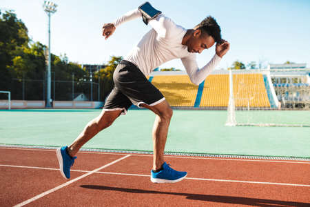 Side view of young attractive African American sportsman running on racetrack at city stadium