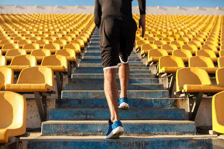 Close up back view of young sportsman running among empty stadium seats
