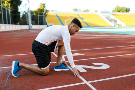 Young attractive African American sportsman preparing for running on racetrack at city stadium
