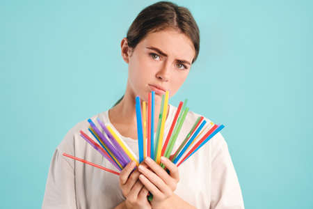 Upset girl holding colorful plastic straws in hands sadly looking in camera over colorful background. Stop using plastic straws