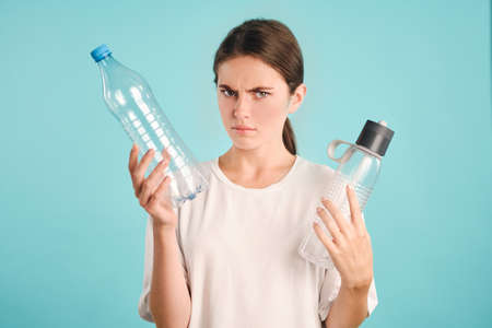 Serious girl angrily looking in camera holding eco and plastic bottles in hands over colorful background