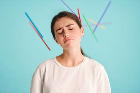 Upset tired girl with plastic straws around sadly posing over colorful background. Stop using plastic straws