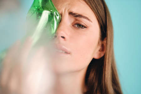 Close up depressed girl covering face with empty plastic bottles ruefully looking in camera over colorful background