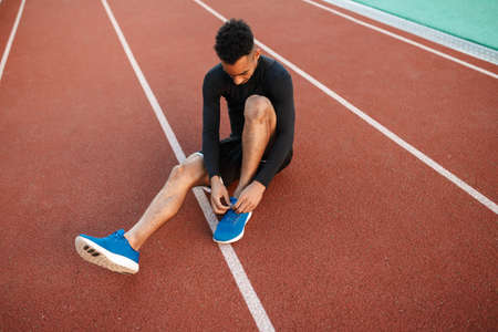 Young African American sporty man tying shoelaces on sneakers on racetrack at stadium