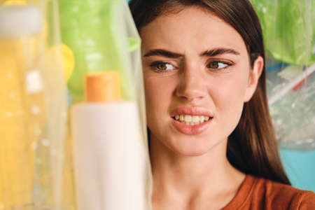 Close up irritated girl squeamishly looking on eco bags with plastic waste over colorful background