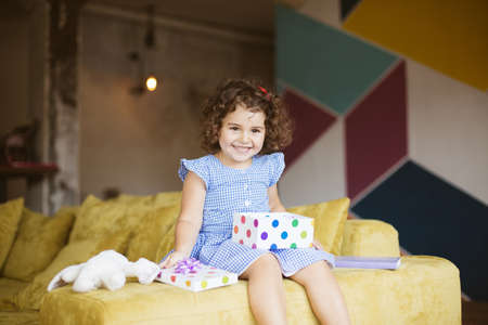 Pretty smiling little girl with dark curly hair in blue dress with gift box on knees happily looking aside on sofa at home