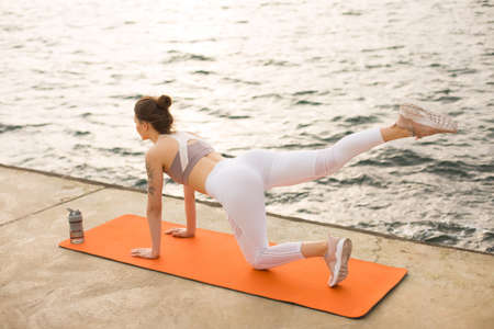 Young cool woman from back practicing yoga with sport bottle near by the sea. Beautiful girl in sporty top and white leggings doing sport exercises on orange yoga mat with sea view on background