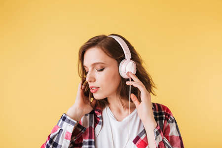 Portrait of beautiful pensive lady in colorful shirt standing and listening music in headphones on over pink background.
