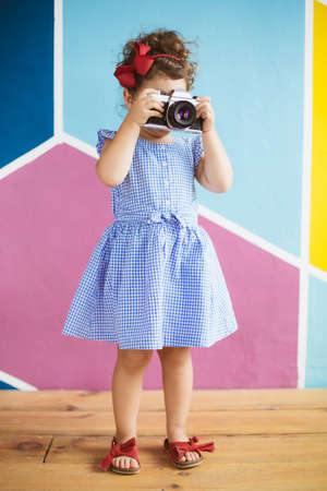 Cute little girl with dark curly hair in blue dress playfully covering face with retro camera over colorful background