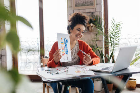 Young cheerful woman with dark curly hair sitting at the table, happily showing fashion illustrations in laptop spending time in modern cozy workshop with big windows Фото со стока