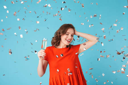 Portrait of beautiful lady in dress standing with champagne, and happily looking aside with confetti around on over pink background