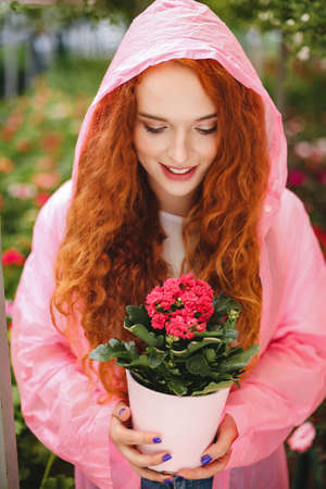 Young smiling lady with redhead curly hair standing in pink raincoat and holding beautiful flower in pot while spending time in greenhouse.