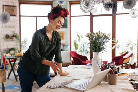 Young gorgeous smiling woman with dark curly hair leaning on table, happily looking in laptop with sketches around spending time in modern cozy workshop with big windows