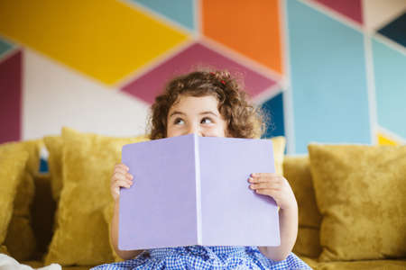 Pretty little girl with dark curly hair in blue dress happily looking aside covering mouth with book on sofa at home
