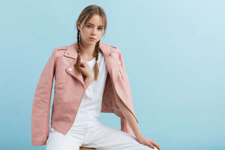 Young attractive pensive girl with two braids in pink leather jacket and white jeans dreamily looking in camera over blue background