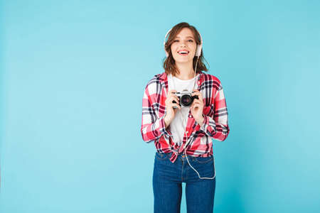 Portrait of young beautiful lady in headphones standing with little retro camera in hands on over pink background Фото со стока