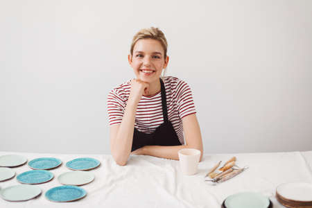 Pretty smiling girl in black apron and striped T-shirt sitting at the table with handmade mug and plates, happily looking in camera at pottery studio