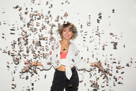 Beautiful smiling girl in white shirt happily looking in camera with confetti around over white background