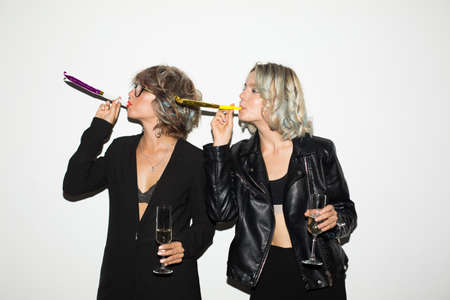 Two beautiful girls in black jackets holding glasses of champagne using noisemakers together over white background Stock Photo