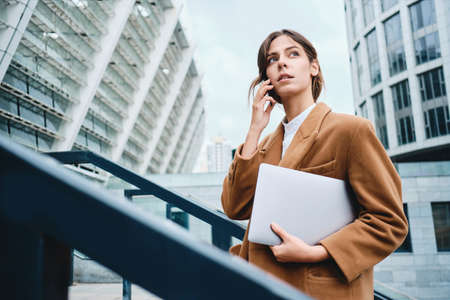 Young pensive businesswoman in coat with laptop talking on cellphone thoughtfully looking away outdoor