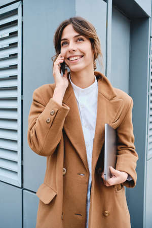 Young pretty smiling businesswoman in coat with laptop happily talking on cellphone outdoor 版權商用圖片